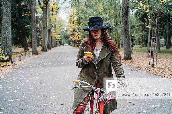 Young woman with long red hair on bicycle looking at smartphone in autumn park  Florence  Tuscany  Italy