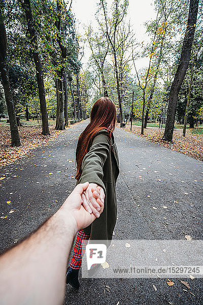 Young woman with long red hair holding boyfriend's hand in autumn park  personal perspective