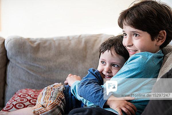 Großer Bruder umarmt Kleinkind auf Sofa