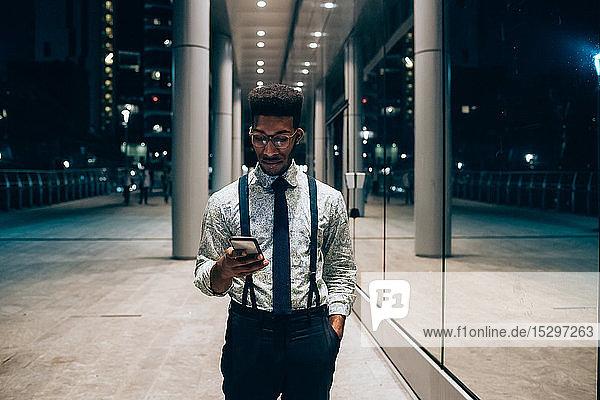 Geschäftsmann mit Smartphone  geht an Spiegelwand eines Bürogebäudes vorbei  Mailand  Lombardei  Italien