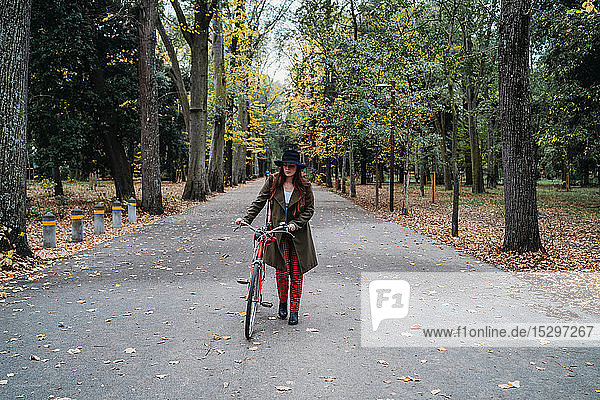 Young woman with long red hair pushing bicycle in tree lined autumn park  Florence  Tuscany  Italy