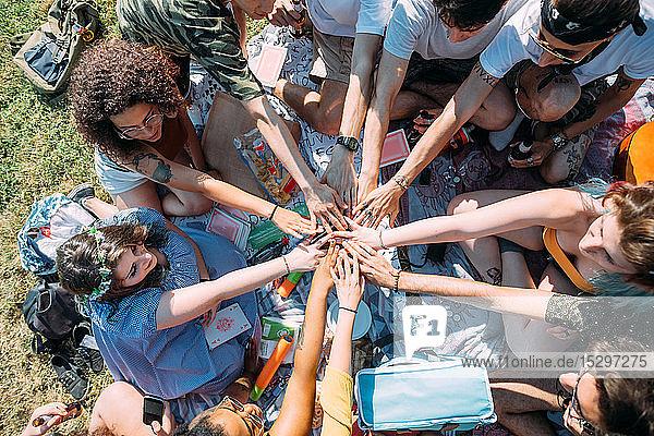 Gruppe von Freunden  die im Park im Kreis die Hände überlappen