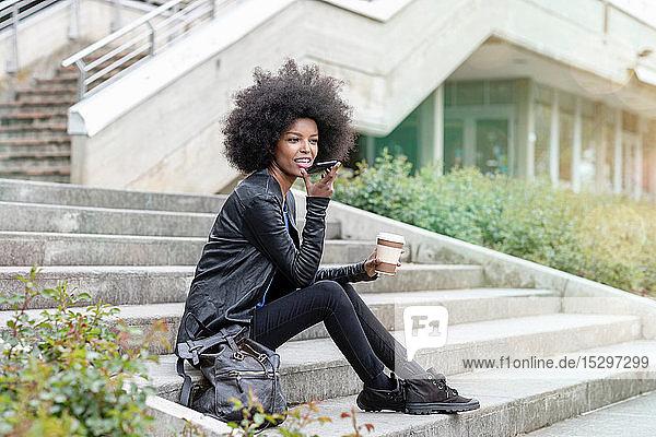 Junge Frau mit Afro-Haaren sitzt auf einer Stadttreppe und spricht mit einem Smartphone