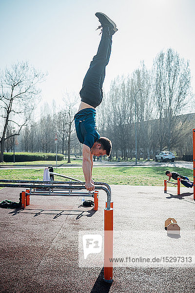Calisthenics at outdoor gym  young man doing handstand on parallel bars
