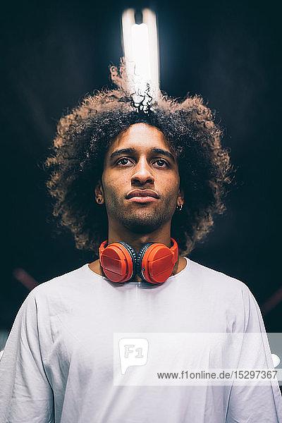 Junger Mann mit Kopfhörern um den Hals