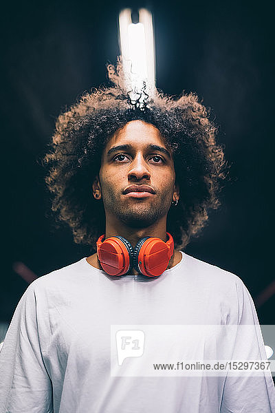 Young man with headphones around neck