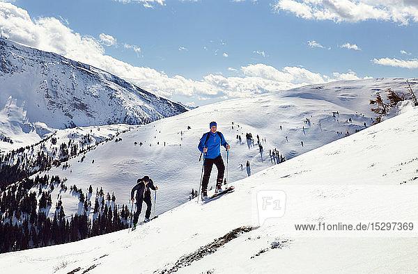 Älteres Skifahrerpaar zieht auf schneebedeckten Berg  Steiermark  Tirol  Österreich