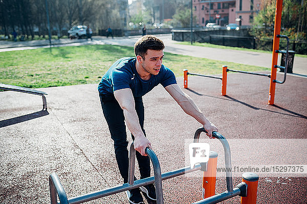 Calisthenics at outdoor gym  young man preparing to use exercise equipment