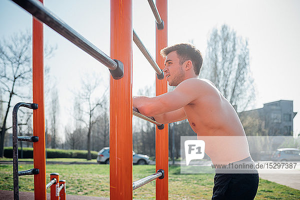 Calisthenics at outdoor gym  bare chested young man leaning on exercise equipment taking a break