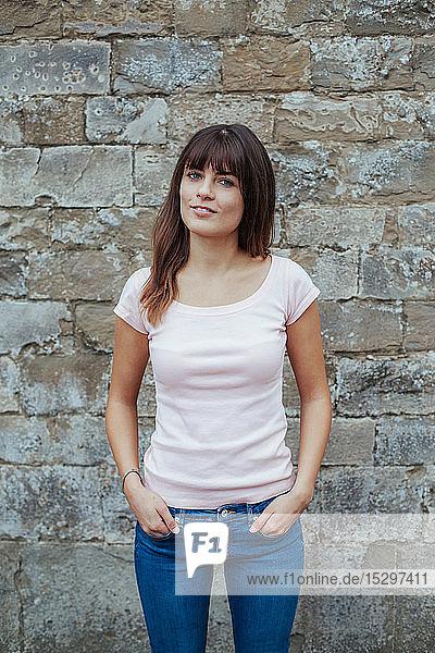 Porträt einer jungen Frau gegen Steinmauer
