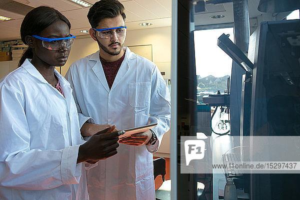 Junge Wissenschaftlerinnen und Wissenschaftler sehen sich wissenschaftliche Geräte im Labor an