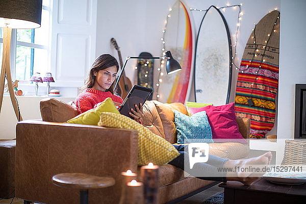 Junge Frau entspannt sich auf Wohnzimmer-Sofa und schaut auf digitales Tablet