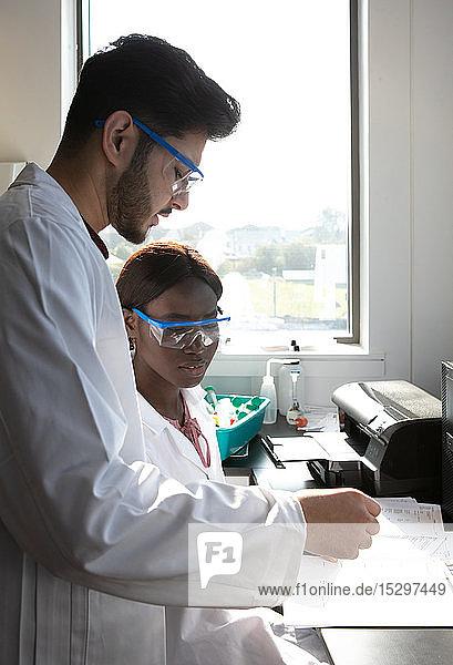 Junge Wissenschaftlerinnen und Wissenschaftler sehen sich Papierkram im Labor an