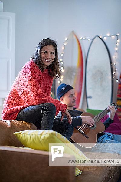 Junge Frau sitzt auf einem Wohnzimmersofa und ein junger Mann spielt Gitarre