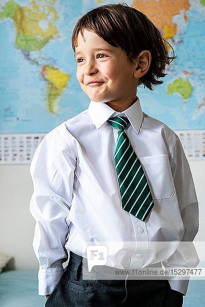 Porträt eines Jungen in Schuluniform  Weltkarte im Hintergrund