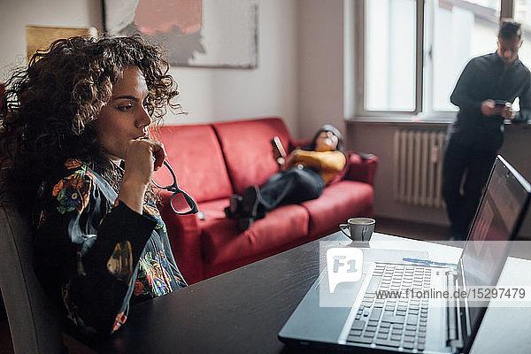 Frau benutzt Laptop  Freunde entspannen sich im Hintergrund im Home-Office