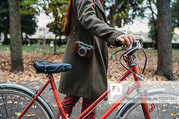 Young woman pushing bicycle in autumn park  neck down