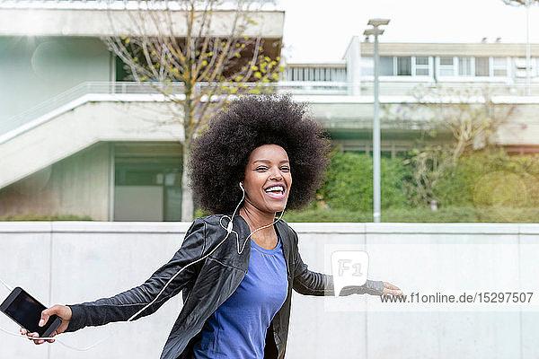 Glückliche junge Frau mit Afrofrisur in der Stadt  die lacht und zu Smartphone-Musik tanzt