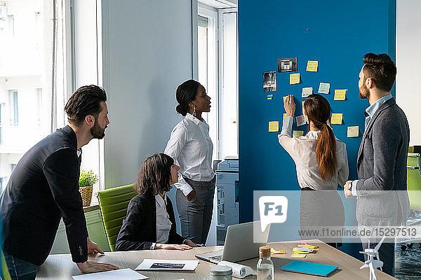 Kreatives Brainstorming mit Haftnotizen im Büro für junge Männer und Frauen