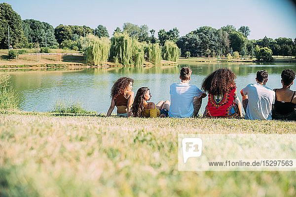 Eine Gruppe von Freunden genießt die Aussicht auf den See im Park