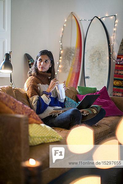 Junge Frau in Strickpulli entspannt auf Wohnzimmersofa mit Getränk