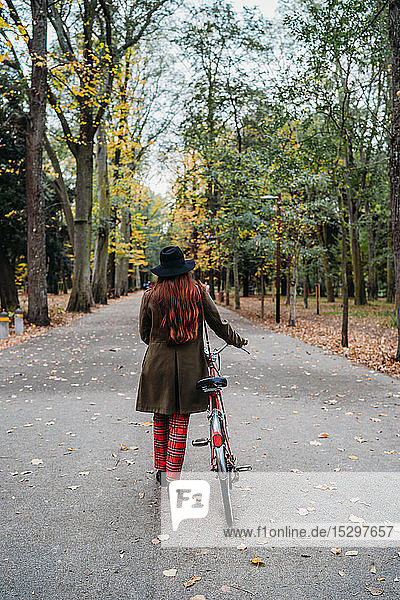 Young woman with long red hair pushing bicycle in tree lined autumn park  rear view  Florence  Tuscany  Italy
