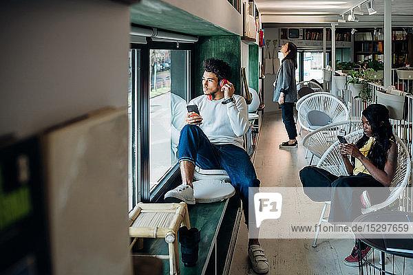 Junger Mann hört Kopfhörer am Fensterplatz eines Cafés