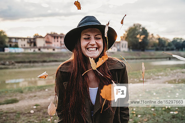 Young woman with long red hair laughing amongst floating autumn leaves on riverside  Florence  Tuscany  Italy