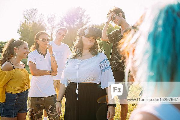 Gruppe von Freunden beobachtet Frau  die im Park in ein VR-Headset schaut