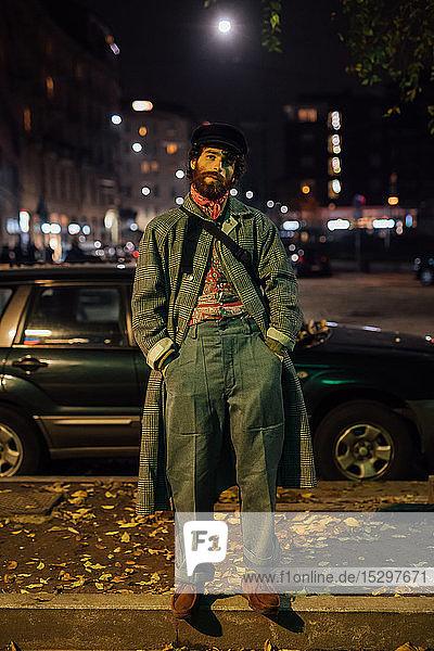 Bärtiger junger Mann lungert auf der Straße herum
