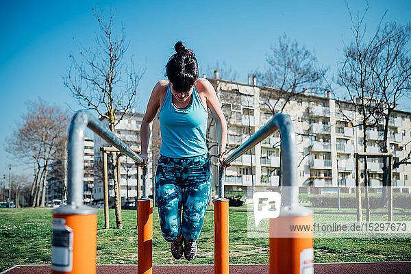 Gymnastikkurs im Freien  junge Frau macht Push-Ups am Barren