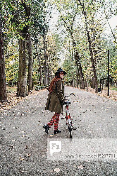 Young woman with long red hair looking over her shoulder while pushing bicycle in autumn park  full length  Florence  Tuscany  Italy