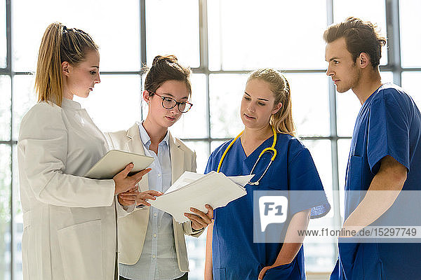 Young female and male junior doctors looking at medical records in hospital