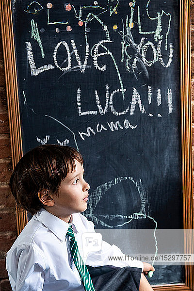 Junge in Schuluniform neben der Tafel zu Hause