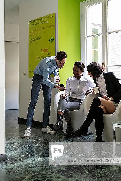 Unternehmerinnen und Unternehmer machen eine Pause und schauen sich im Büro ein Smartphone an