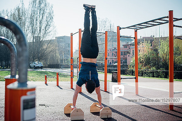 Calisthenics at outdoor gym  young man doing hand stand on exercise equipment  rear view