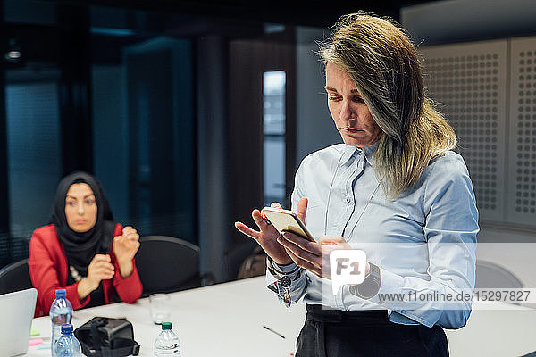 Businesswoman using smartphone at meeting in office
