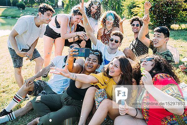 Eine Gruppe von Freunden nimmt Selfie  spielt mit Konfetti im Park