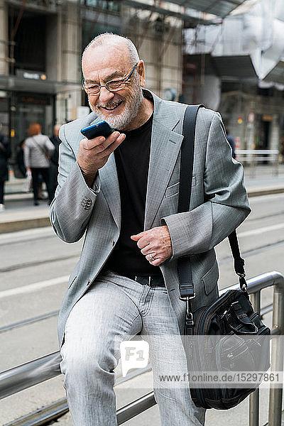 Geschäftsmann spricht mit einem Smartphone auf dem Bürgersteig  Mailand  Lombardei  Italien