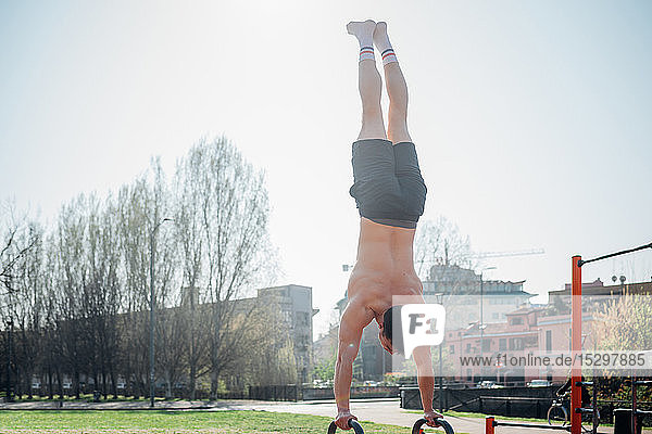 Calisthenics at outdoor gym  young man doing handstand on exercise equipment  rear view