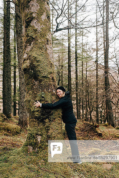 Woman hugging tree  Trossachs National Park  Canada