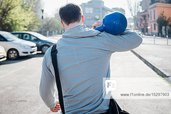 Calisthenics in park  young man carrying kettlebell over his shoulder  rear view