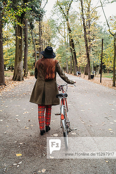 Young woman with long red hair pushing bicycle in autumn park  rear view full length  Florence  Tuscany  Italy