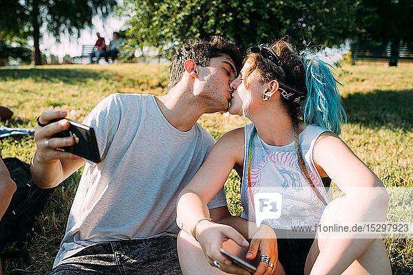 Küssen zu zweit  Smartphone im Park benutzen