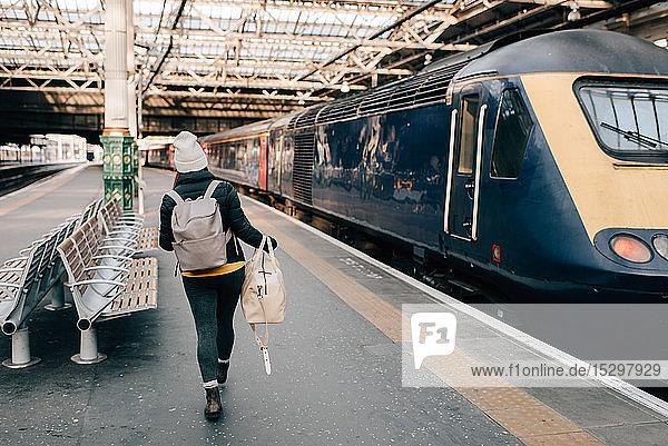 Frau geht am Bahnsteig zum Zug  Edinburgh  Schottland