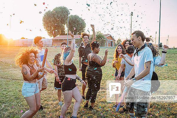 Gruppe von Freunden tanzt  spielt mit Konfetti im Park