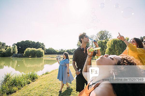 Gruppe von Freunden bläst Blasen im Park