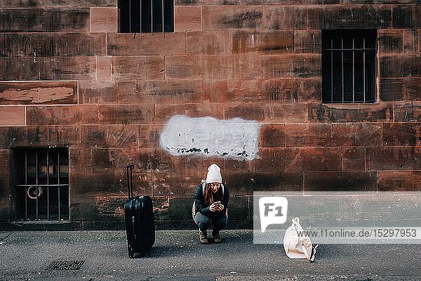 Frau schreibt mit Handy und Gepäck am Bordstein  Edinburgh  Schottland