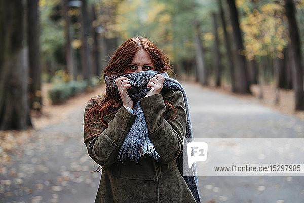 Young woman with long red hair in autumn park covering mouth with scarf  portrait