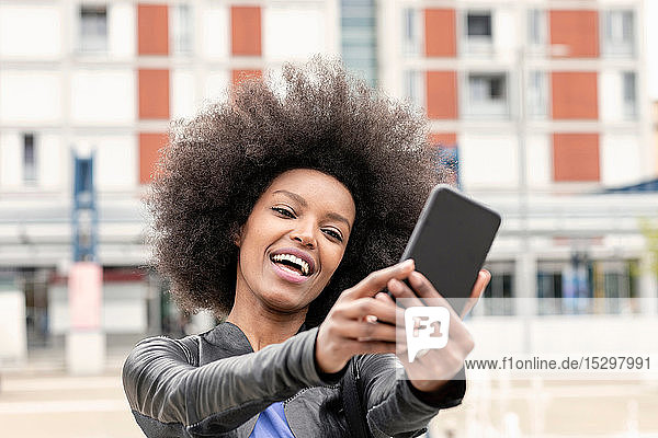 Happy young woman with afro hair in city  taking smartphone selfie